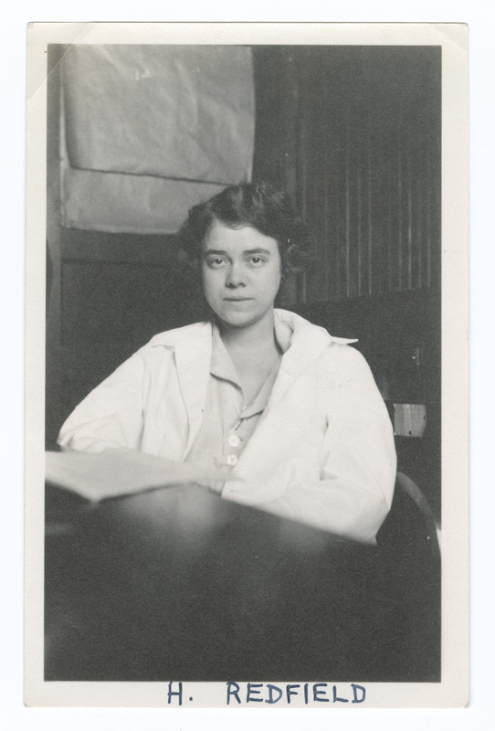 Helen Redfield, seated in an office or lab, wearing a white lab coat